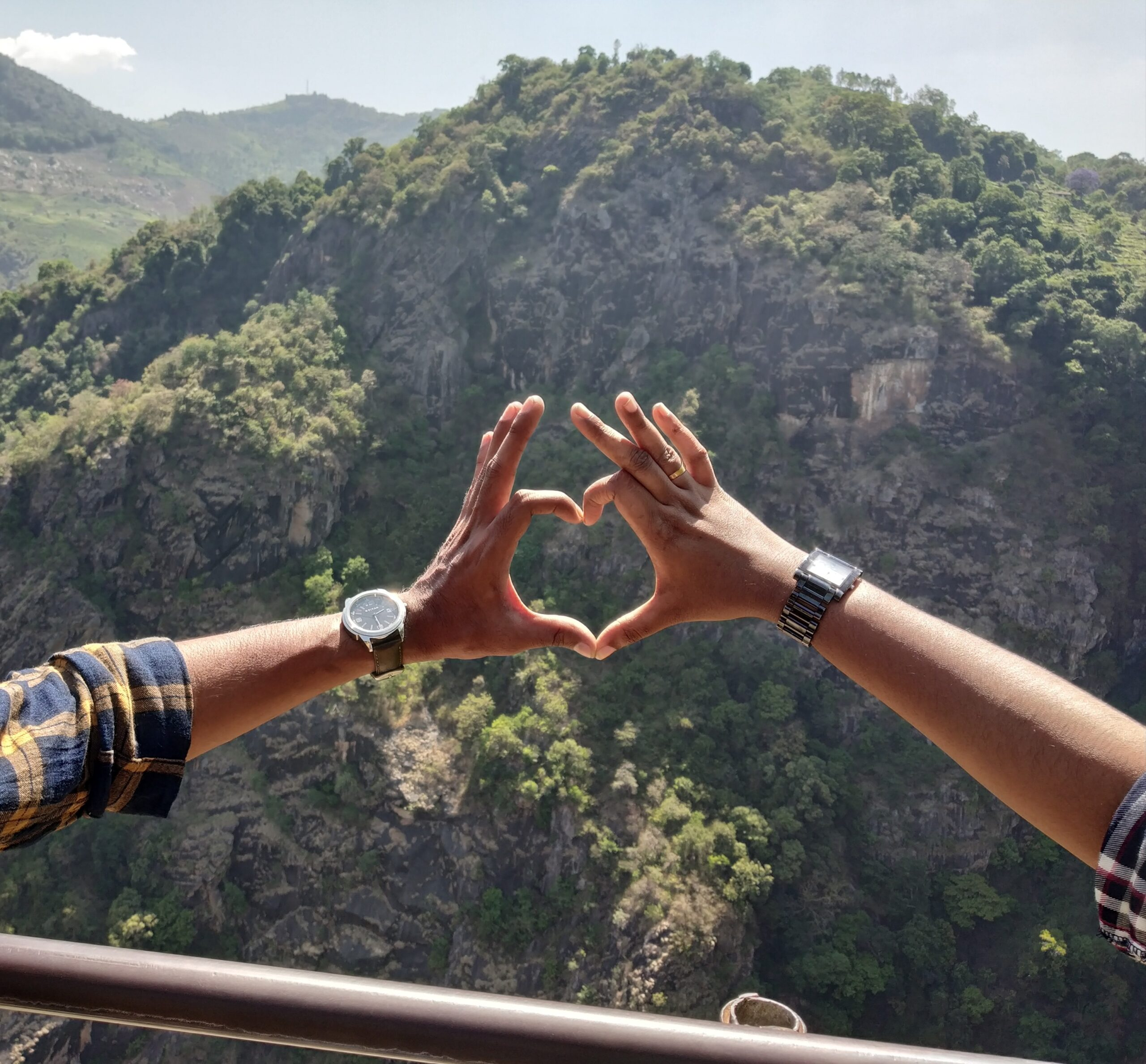two person forming heart shape by hands